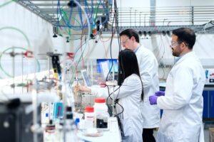 研究室で研究をしている男性二人と女性一人